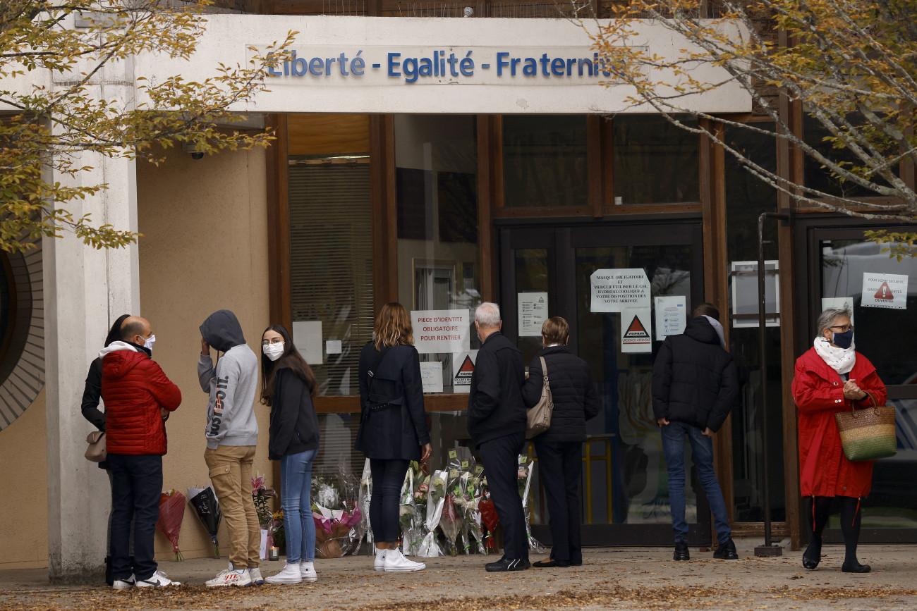 Conflans Sainte-Honorine, 2020. október 17. Tanulók és szülők leróják kegyeletüket a Bois d'Aulne középiskolánál 2020. október 17-én, miután az előző nap egy 17 éves csecsen fiú késsel megölte, majd lefejezte az iskola történelemtanárát Párizs északnyugati elővárosa, Conflans-Saint-Honorine egyik utcáján. A tettest a rendőrök agyonlőtték. Korábban a tanár az óráján megmutatta diákjainak a Mohamed prófétáról készült karikatúrákat, amikor a szólásszabadságról beszélt. MTI/EPA/Yoan Valat