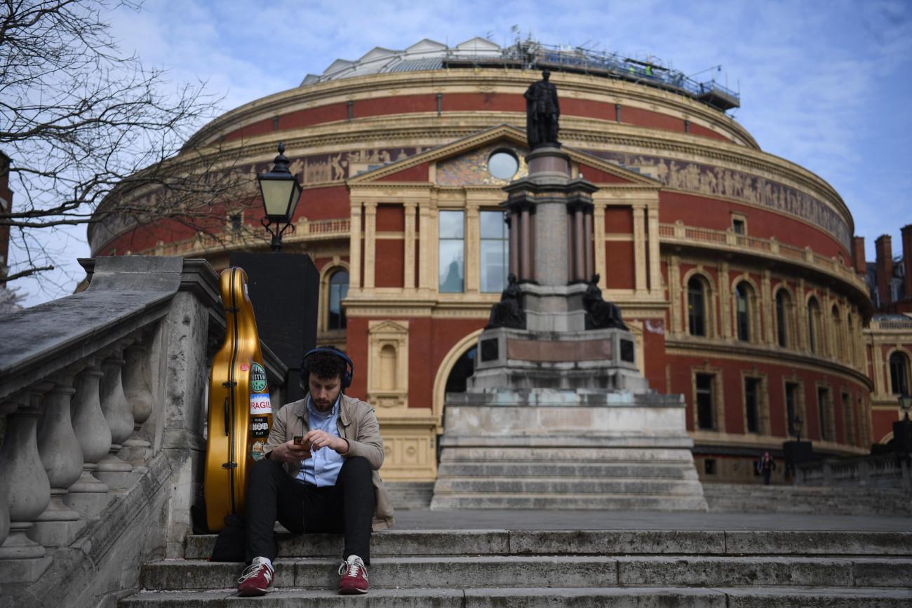 London, 2021. március 29. A 2021. március 29-én közreadott képen egy férfi ül a londoni Royal Albert Hall hangversenyterem épülete előtti lépcsőn 2021. március 24-én. 150 évvel ezelőtt, 1871-ben Viktória királynő nyitotta meg a 6000 néző befogadására alkalmas koncerttermet. MTI/EPA/Neil Hall