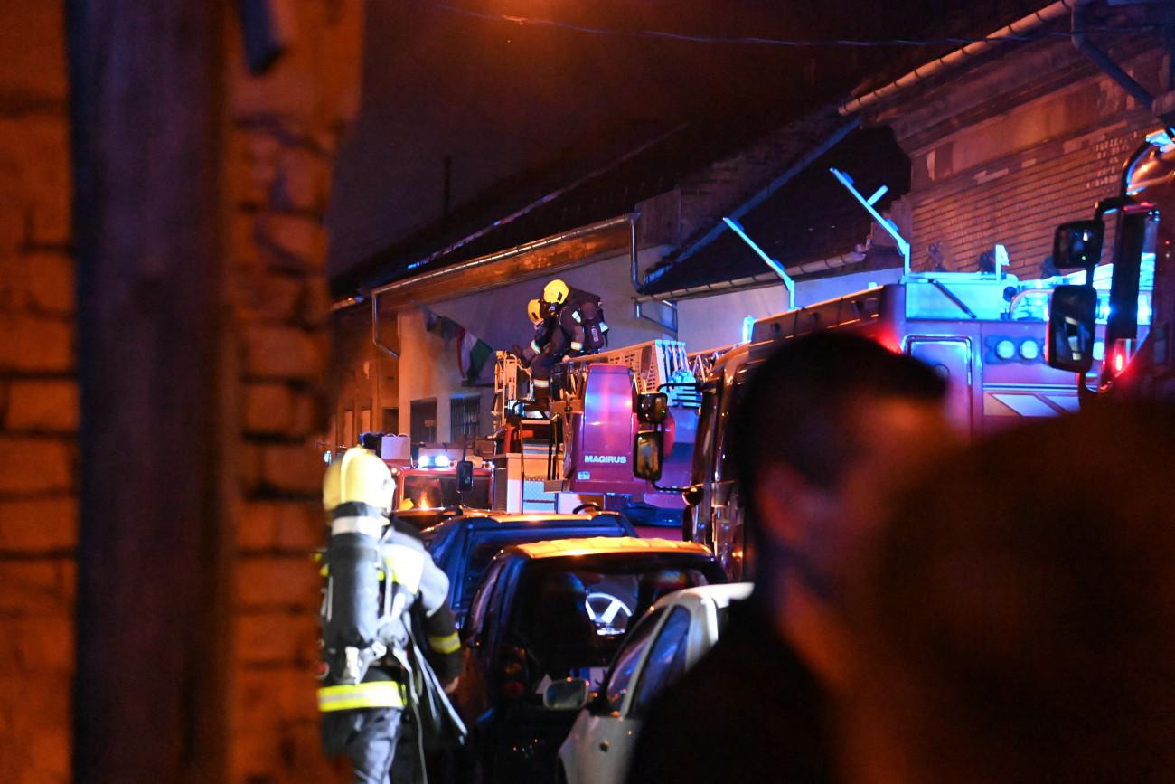 Budapest, 2021. július 18. Tűzoltók a főváros VIII. kerületében, a Koszorú utcában, ahol tűz keletkezett egy munkászállóként működő épület második emeletén 2021. július 18-án hajnalban. A lángok a tetőszerkezetet és a szomszédos épület tűzfalát is elérték. A tűzoltók a tetőről négy embert mentettek le, az érintett épületeket kiürítették. A nagy erőkkel kivonuló tűzoltók nyolc vízsugárral eloltották a tüzet. MTI/Mihádák Zoltán