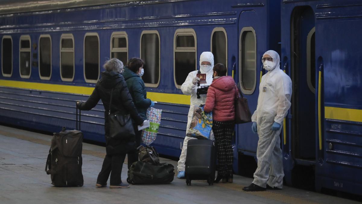 Védőruházatot viselő munkások ellenőrzik utasok iratait a kijevi vasútállomáson 2020. március 27-én. Az ukrán kormány bejelentette, hogy a koronavírus-járvány miatt Ukrajna teljesen leállítja a nemzetközi utasszállítást, azaz lezárja határait saját állampolgárai előtt is. Az orosz állami vasúti társaság különvonatot indít az orosz állampolgárok Ukrajnából és az ukránok Oroszországból történő hazaszállítására. A mintegy 800 férőhelyes szerelvény a tervek szerint 27-én indul Kijevből és másnap érkezik meg Moszkvába.