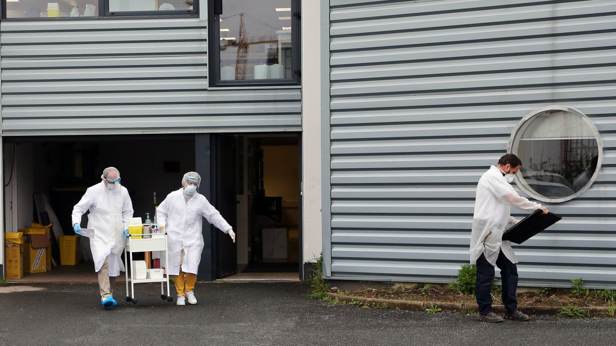 Védőruhát viselő egészségügyi dolgozók teszteléshez készülődnek a délnyugat-franciaországi Anglet város biológiai laboratóriuma előtt létesített autós tesztállomáson 2020. április 20-án, a koronavírus-járvány idején.