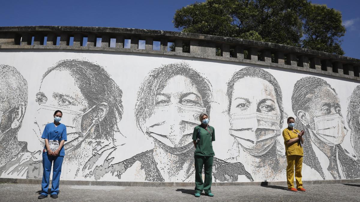Raquel Queiros, Maria Joao és Idalina Ramos egészségügyi dolgozók (b-j) az őket ábrázoló portrék előtt, a portugáliai Portóban 2020. június 19-én. A VHILS művésznéven alkotó Alexandre Farto graffitikészítő tíz egészségügyi dolgozó portréját festette meg a Sao Joao Kórház falára, az irántuk érzett tisztelete és hálája jeléül, amiért erejüket megfeszítve gyógyítják a koronavírus-járvány betegeit.