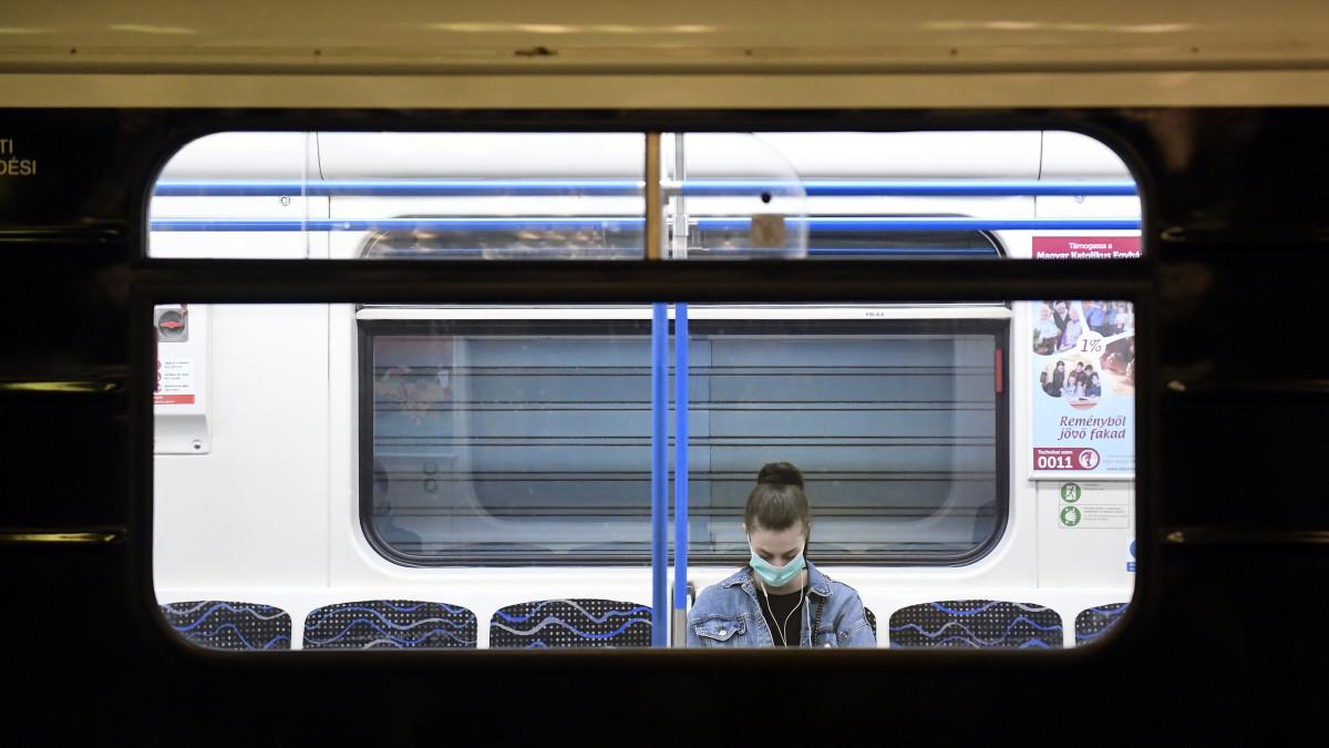 Védőmaszkot viselő utas a 3-as metró Deák téri állomásán 2020. március 19-én. A koronavírus-járvány miatt jelentősen csökkent az utazók száma a közösségi közlekedés járatain.